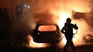 Un bomber intenta apagar les flames d'un cotxe incendiant-se a Jerusalem (EFE / Abir Sultan)