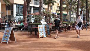 Dos turistes passen per davant de la terrassa d'un restaurant al passeig Jacint Verdaguer de Lloret