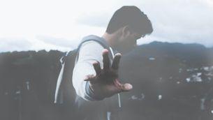 Home amb motxilla en una muntanya