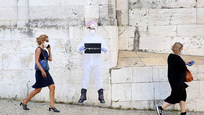 Dues dones amb mascareta passen davant una pintada que demana que es quedin a casa a Lisboa (Europa Press/Pedro Fiuza)