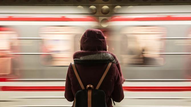 Una jove contempla el pas del tren en una estació