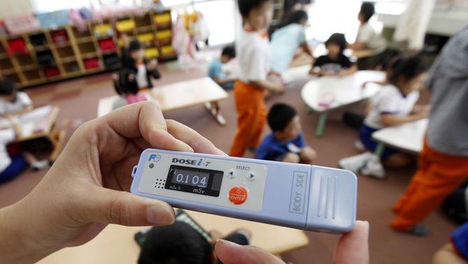 Una mestra mesura el nivell de radiació en una escola de primària fora dels 20 km de distància de Fukushima. (Foto: Reuters)