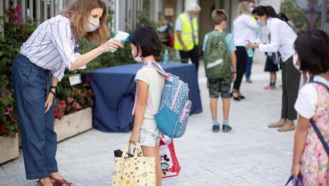 Una mestra pren la temperatura a una alumna a l'entrada d'un centre escolar a Esplugues de Llobregat