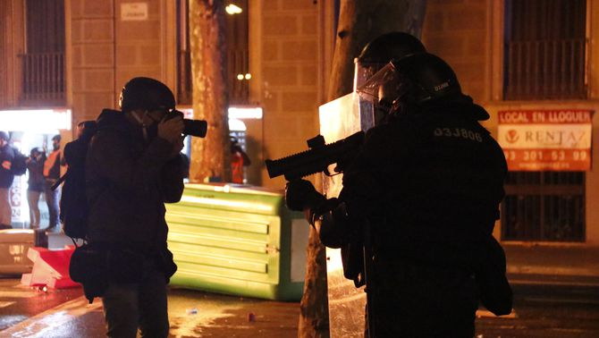 Un periodista fotografia un agent dels Mossos amb una llançadora de foam, durant les protestes per Pablo Hasél (ACN / Blanca Blay)