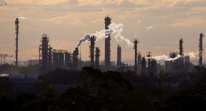 Un avió i ocells davant de les emissions de xemeneies en una planta química vora Sidney