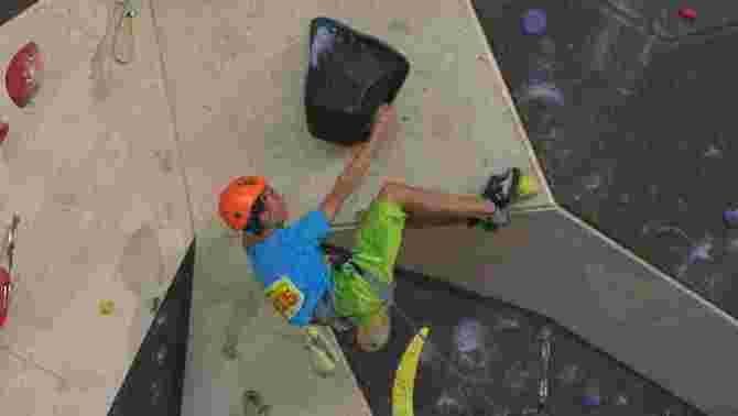 Un esportista federat fent escalada a un rocòdrome.