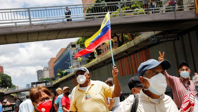 Un home enarbora una bandera veneçolana en una protesta al carrer, envoltat d'altres jubilats que es manifesten