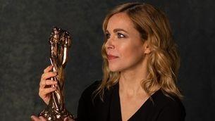 """Tània Sarrias, presentadora de """"Les cares dels Gaudí"""", mirant-se una estatueta dels Gaudí que té a les mans"""