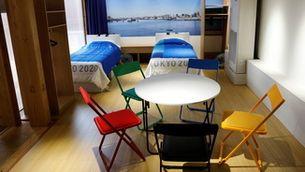 Una de les habitacions de la vila olímpica amb taula i cadires