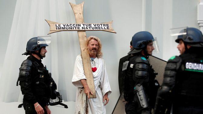 Un negacionista contrari a les vacunes, vestit com Jesús i amb una creu, durant una protesta a París