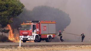 Els bombers treballen per apagar el foc a la carretera de Matalascañas a Mazagón (EFE)