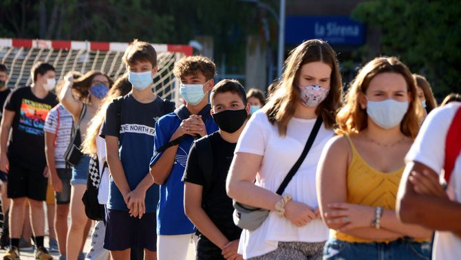 Pla mitjà d'alumnes de 4t d'ESO de l'institut Martí i Franquès de Tarragona en filera i amb mascareta durant la presentació al pati e…