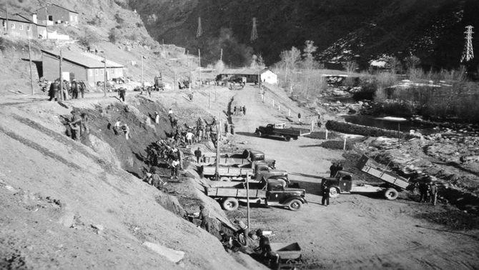 Pla general del formiguer de treballadors i camions condicionant les obres de desviació de la carretera cap a Esterri d'Àneu, esplanant la central d'Escaló l'any 1950. (horitzontal)