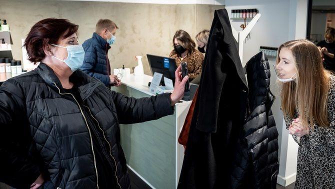 Una clienta mostra el 'coronapassi' en entrar en una perruqueria de Koege, a Dinamarca, a l'abril