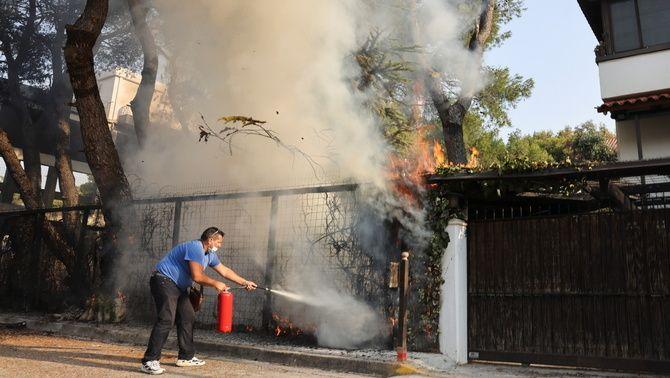 Un home intenta apagar un foc a tocar de casa seva en un barri d'Atenes