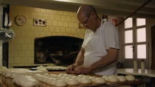 Un home fent pa en una fleca