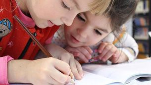 Dues nenes dibuixen en una escola