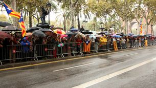 Alguns dels ciutadans que, aixoplugats sota els paraigües, han acudit a donar suport a Joana Ortega a les portes del TSJC