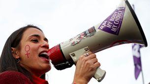 Noia amb un símbol de dona a la galta i un megàfon en una manifestació a Brussel·les contra la violència masclista