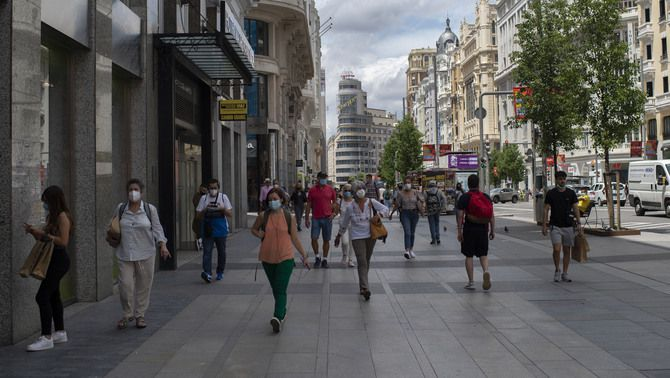 Diverses persones amb mascareta, passejant divendres passat per Madrid