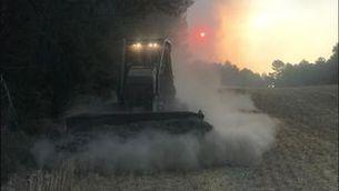 Un tractor llaurant el camp ben d'hora al matí per evitar el pas de les flames