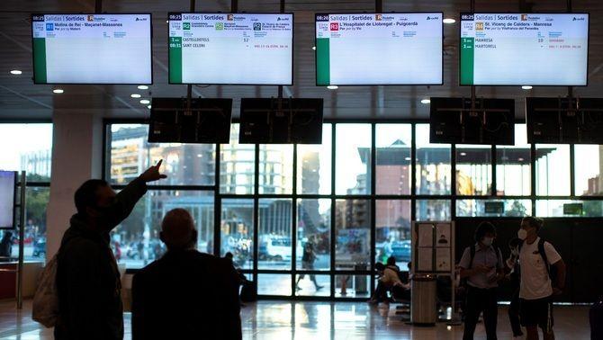 Diversos usuaris consulten els horaris dels trens a l'estació de Sants