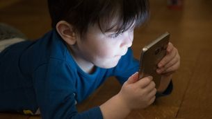Un nen amb un telèfon intel·ligent.