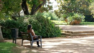 Una dona asseguda a un parc