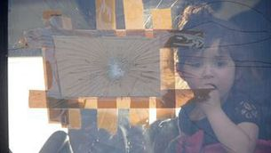Una nena refugiada siriana mira per la finestra d'un autobús a la frontera (Reuters)