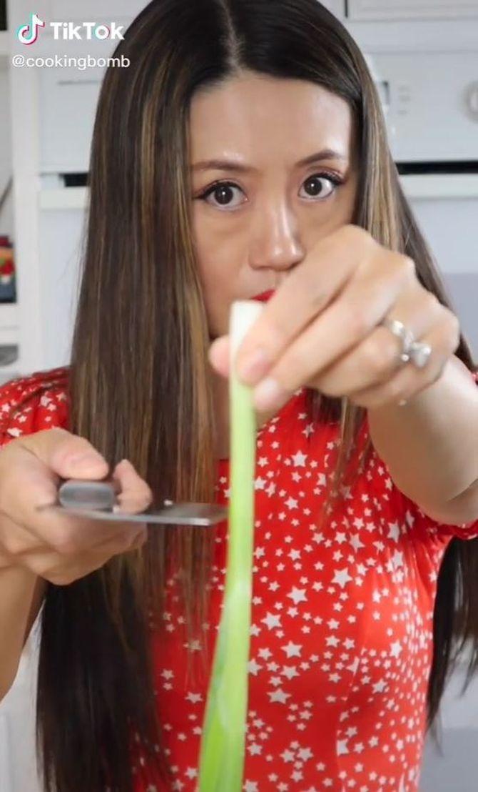 La cuinera talla una ceba tendra amb un ganivet