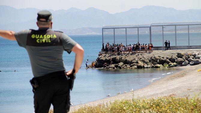 Un agent de la Guàrdia Civil observa migrants arribats al Tarajal