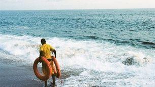 Home davant del mar amb dos flotadors salvavides