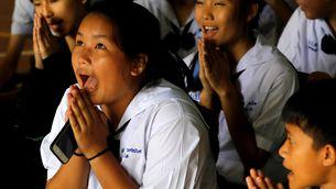 Companys de classe dels nens atrapats a la cova preguen després de saber que alguns ja han estat rescatats (Reuters)