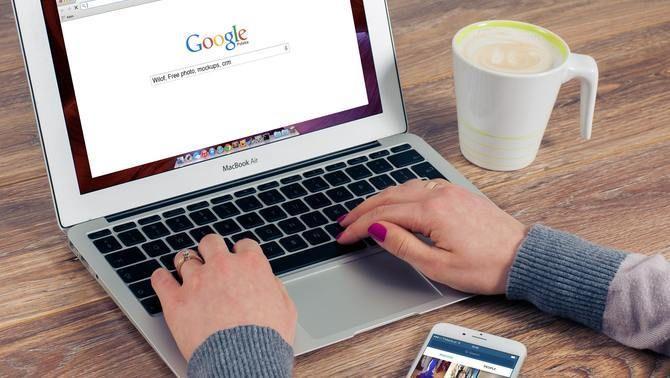 Una persona tecleja un ordinador portàtil on es veu la pàgina d'inici del cercador Google, a prop hi té una tassa de cafè i un telèfon mòbil
