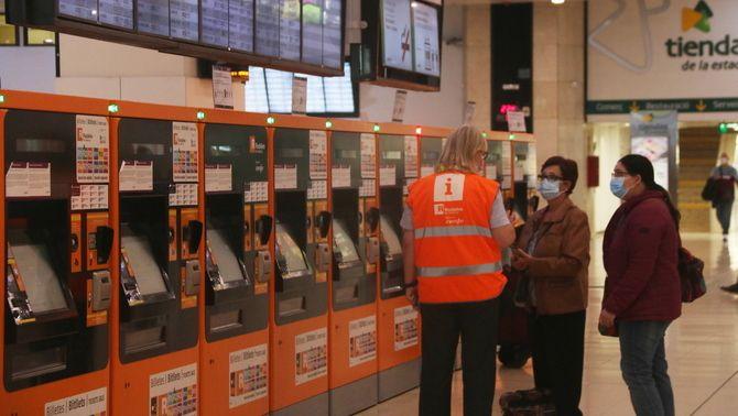 Un treballador de Renfe informa dos usuaris a l'estació de Sants