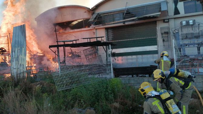 Pla oberts dels Bombers de la Generalitat treballant per apagar l'incendi de la nau industrial de la Canonja. Imatge del 14 de març del 2021 (H…
