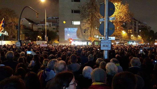 Diversa gent concentrada a les Corts mirant el partit, projectat a l'edifici de la biblioteca Miquel Llongueras