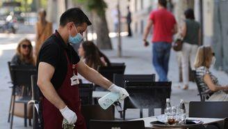 Un cambrer neteja una terrassa d'un bar, seguint els protocols de seguretat per la Covid (EFE/Mariscal)