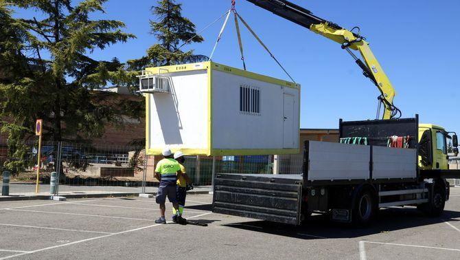 Pla obert on es poden veure dos operaris descarregant una caseta de treball per a l'obra de l'hospital annex a l'Arnau de Vilanova pe…