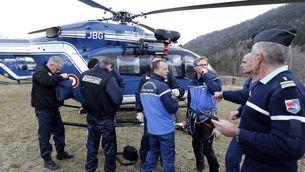 Gendarmes francesos al voltant d'un helicòpter de rescat, en una zona pròxima al lloc de l'accident (EFE)
