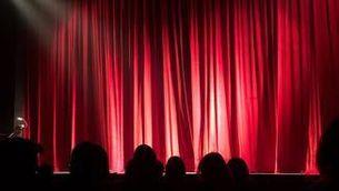 Públic davant la cortina vermella d'un teatre