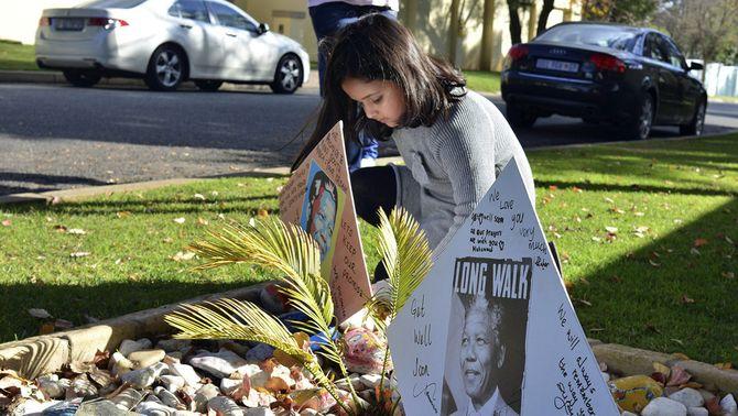Una nena deixa un missatge de suport davant la casa de Mandela.