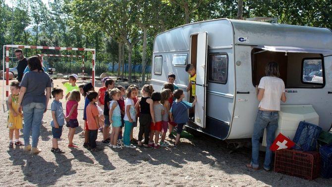 Els nens de l'escola fan cua per entrar a la Bibliovana, aparcada al pati de l'escola.