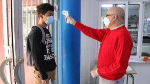 Un mestre pren la temperatura a un alumne a l'entrada de l'institut
