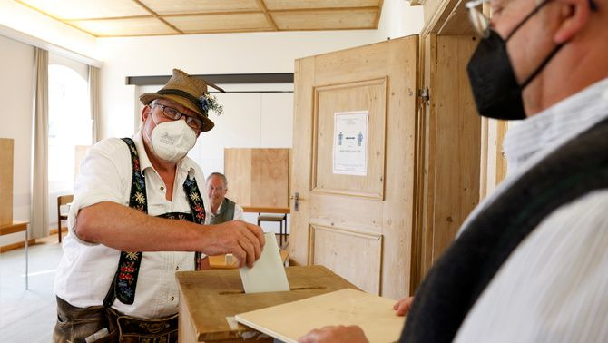 Un home amb el vestit tradicional bavarès vota a Benediktbeuern, aquest diumenge