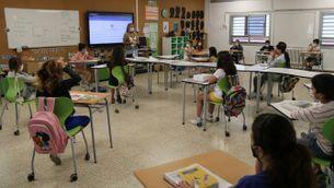 Professora amb mascareta fent classe a alumnes de primària