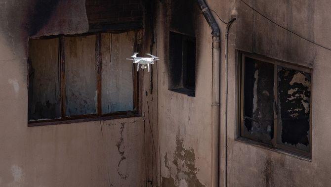 Un dron grava imatges de la nau de Badalona incendiada, aquest dijous (EFE / Enric Fontcuberta)