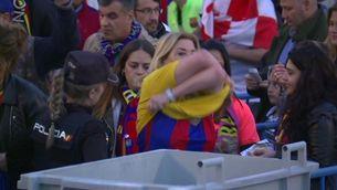 Una dona es treu una samarreta groga davant una policia nacional, aquest dissabte, abans de la final de la Copa del Rei