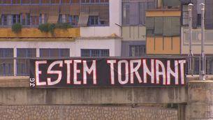 """cartell que posa """"Estem tornant"""""""