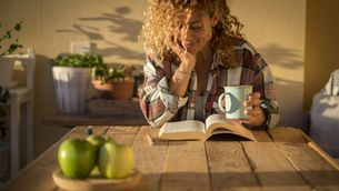 Dona en una terrassa que pren un cafè i llegeix un llibre al sol